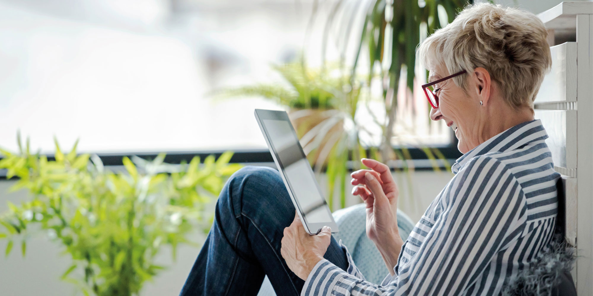 Retiree relaxing, using a tablet